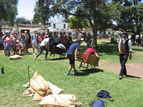 A crazy wheelbarrow race is underway. It's hard not to fall out when you turn!