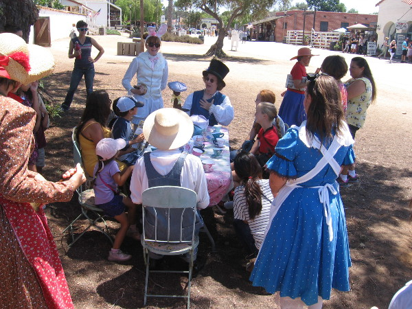 Young people were enjoying a Mad Hatter tea party, with Alice and other Wonderland characters!